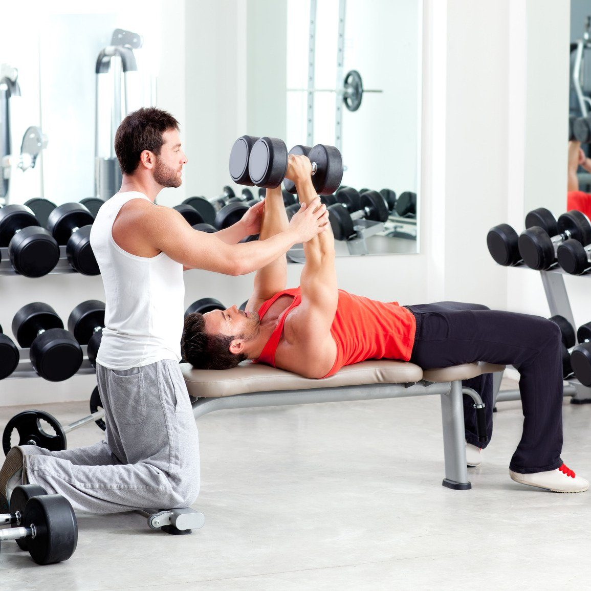 gym personal trainer man with weight training equipment