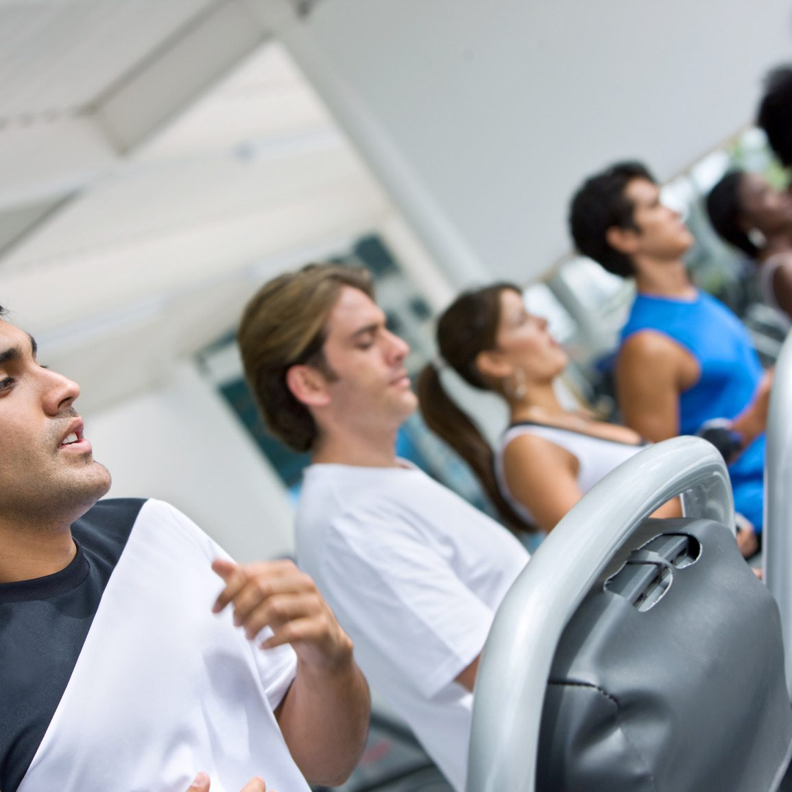 group of people at the gym doing exercise on the machines