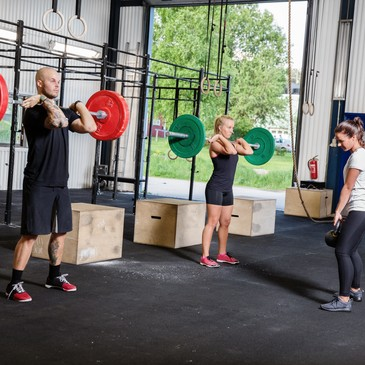 A group trains at a crossfit center. Weight workout at the gym.